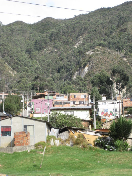 """Makeshift homes like these in or near the mountains are called """"invasiones,"""" and are built mostly by refugees from the countryside. Much of the city's mountains are home to these communities. These tin and brick shacks running up and down the mountain light up like a nativity scene at night."""