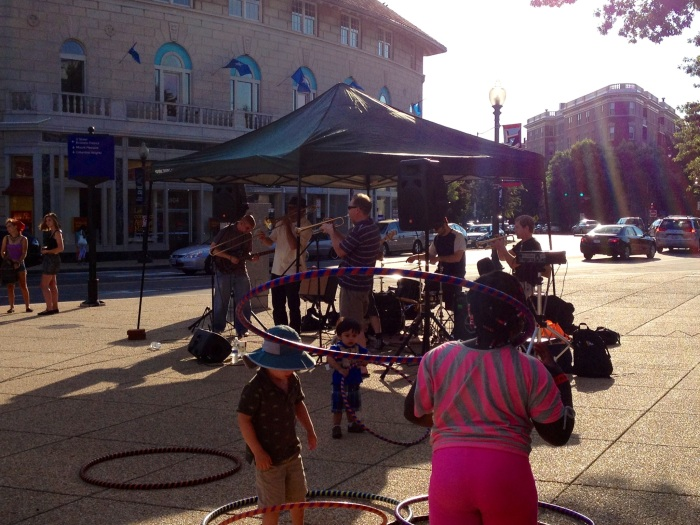 """Kids hula-hooping while The Originators, a Ska/Punk/Raggae band, perform. This groups was part of the free Adams Morgan summer concert series held every Saturday evening in front of the BB&T Bank in the Adams Morgan Neighborhood. We stopped to enjoy the concert for a few minutes and somehow allowed ourselves to get talked into """"making a committment to comit to being volunteers at Adams Morgan Day in September. We did get free t-shirts out of it!"""
