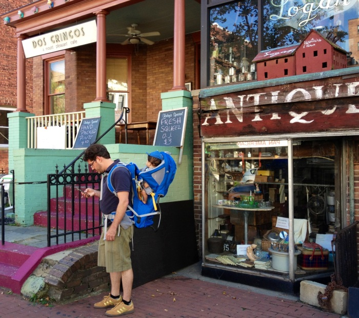 I love this scene: A guy with a baby looking at his iphone -- Dos Amigos Restaurant and Cafe on one side and an antique shop on the other. This is on Mount Pleasant Street, the main commercial street in Mount Pleasant.