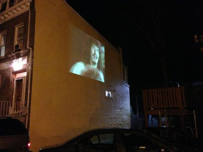 Movie playing on side of house.