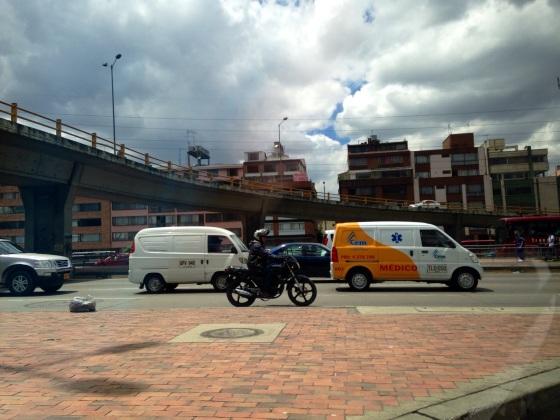 Vans, cars, motorcycles and residential buildings.