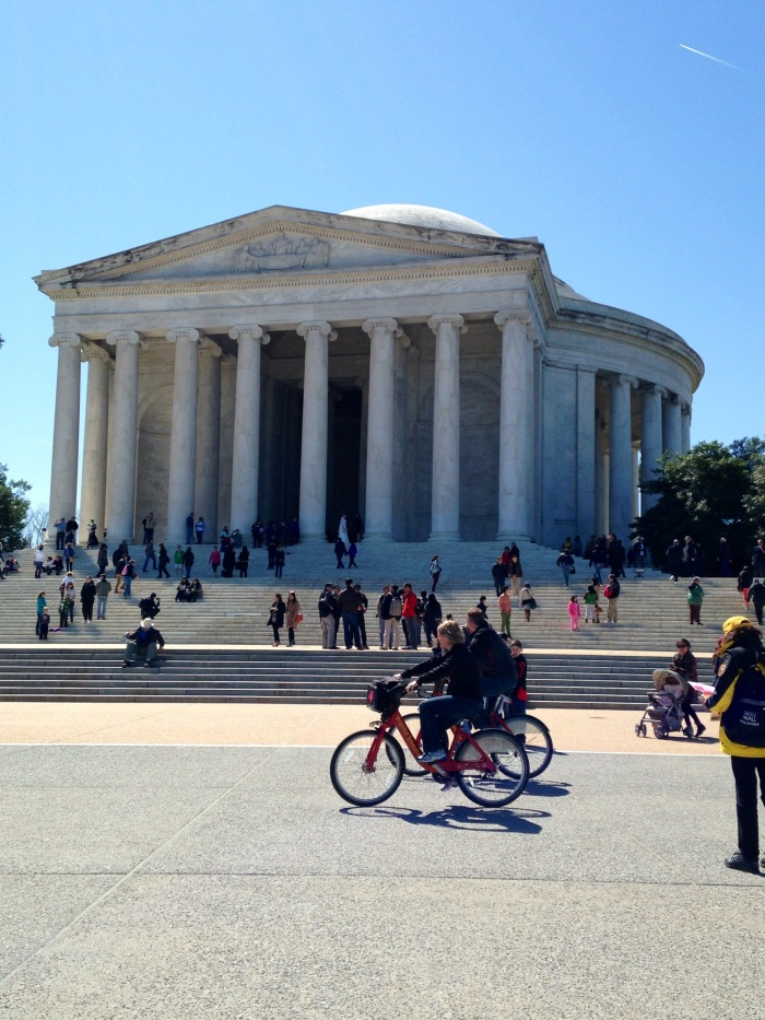 People hanging out, walking and biking near the Jefferson Memorial on an early spring day.